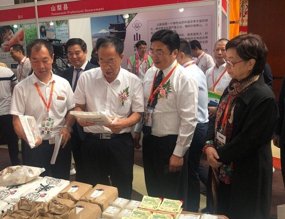 新发地市场董事长张玉玺(左二)一行人参观果蔬展